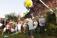 Hispanic Family Breaking Pinata In Backyard