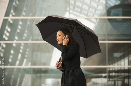 Asian businesswoman with umbrella talking on cell phone