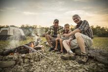Three Generations Of Caucasian Men Roasting Hot Dogs Over Campfire