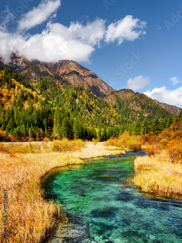 Beautiful river with azure crystal clear water among fall fields