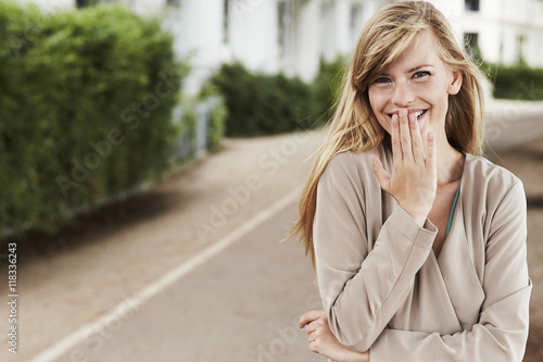 Plakat Shy girl giggling in park, portrait