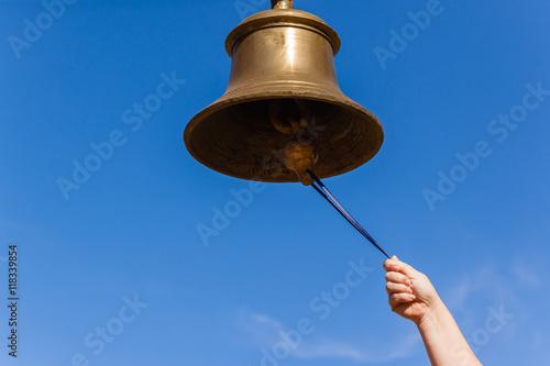 Fotomural Brass Bell Hand closeup ringing notice instrument.