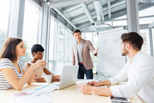 Businessman Making Presentation Of Business Plan Using Flipchart In Office