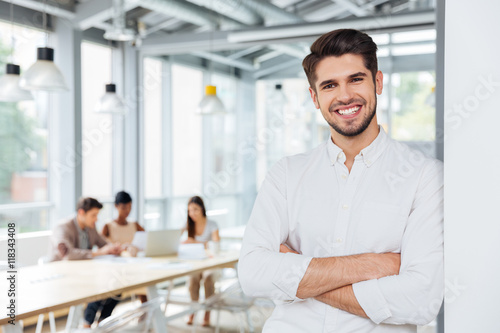 Cheerful businessman standing with arms crossed in office
