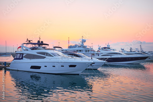Fototapeta Extra Large Luxury yachts rest in the port at sunset