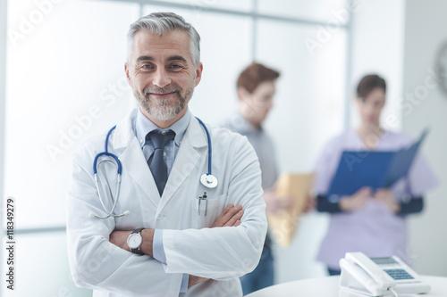 Fotografering Confident doctor at the reception desk
