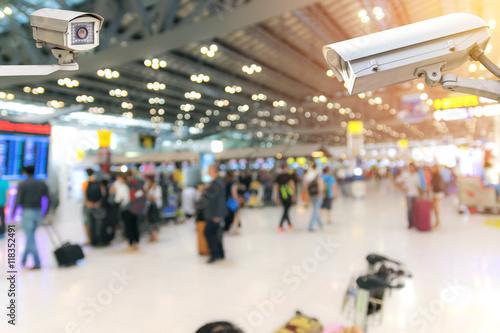 Obraz Closeup CCTV security camera on blurred inside the airport terminal background. - fototapety do salonu