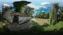360Vr Video Abandoned Building On A River Bank Sunny Summer Day In Park Willow Tree Branches Trees On Opposite Bank Of River White Clouds On Blue Sky