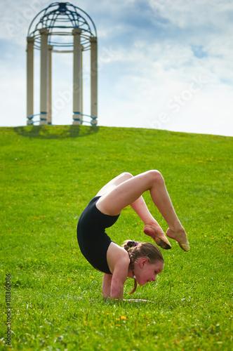 Tuinposter Gymnastiek Young beautiful preteen girl doing gymnastics outdoors