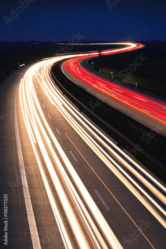 Foto  Winding Motorway at night, long exposure of headlights and taillights in blurred