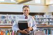 Senior man holding books in library