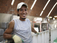 Hispanic Worker Smiling In Fac...