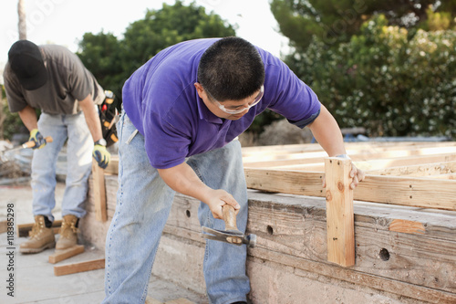 Construction workers hammering lumber