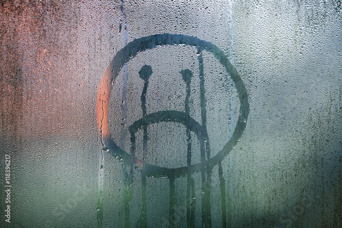 Fotografia Sad upside down smiley hand drawn symbol on wet glass background.