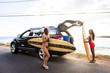 Surfers unloading surfboards from car near beach
