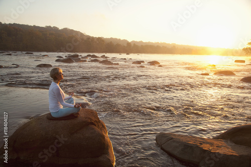 Woman practicing yoga on rock near ocean