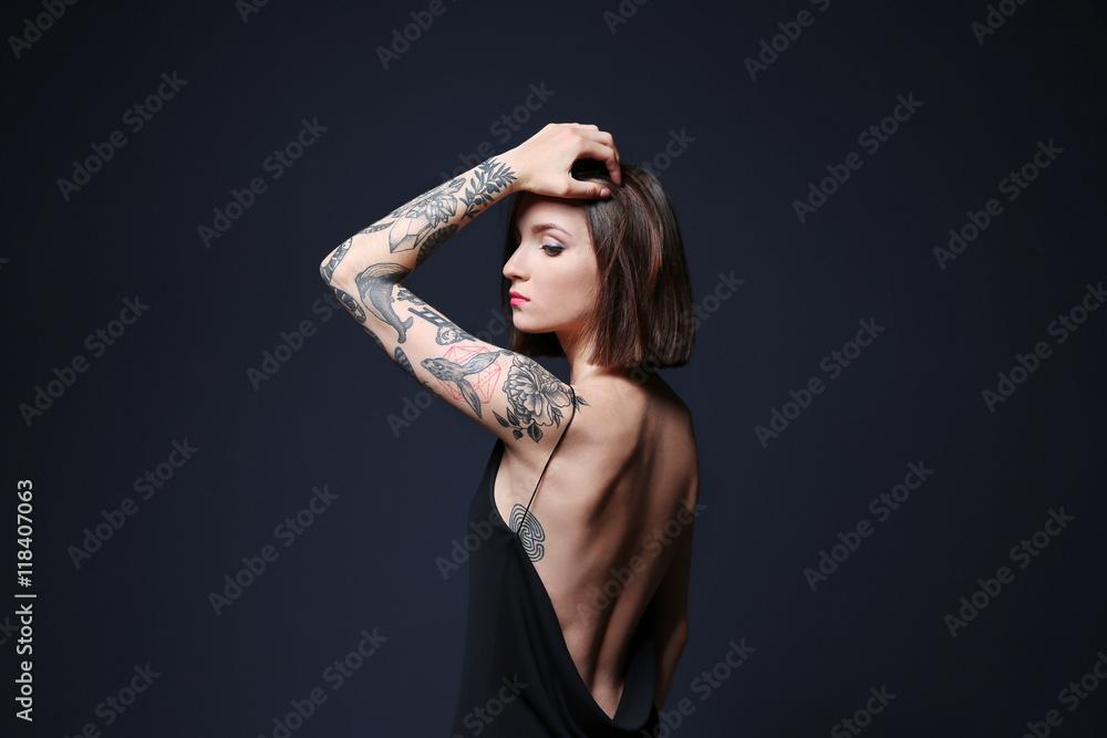 Fototapeta Beautiful young woman with tattoo posing on gray background