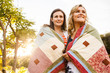 Caucasian teenage girls wrapped in blanket outdoors