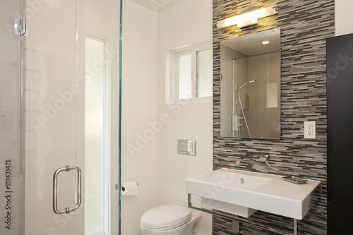 Valokuva  Bathroom with new glass shower and Strip Modern Brick Mosaic Til
