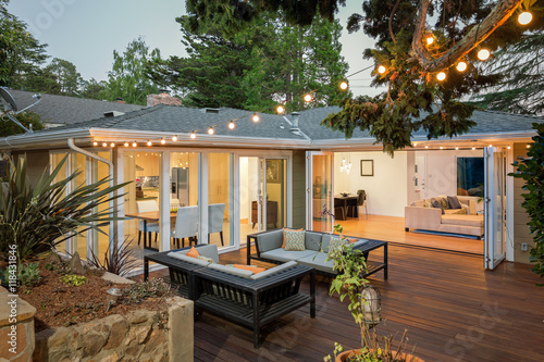 Fotografia  Home with furniture patio / wooden deck at twilight.
