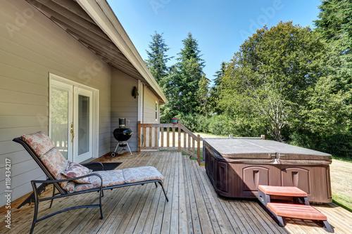 Fototapeta Backyard house exterior with patio area and hot tub on the walkout deck. obraz na płótnie