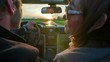 A middle-aged couple is driving towards the sunset on a country road. A woman touches her husban's face. Close-up shot.