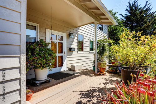 Papiers peints Scandinavie Nice wooden floor porch with flowers and bushes around. Front white entry door.