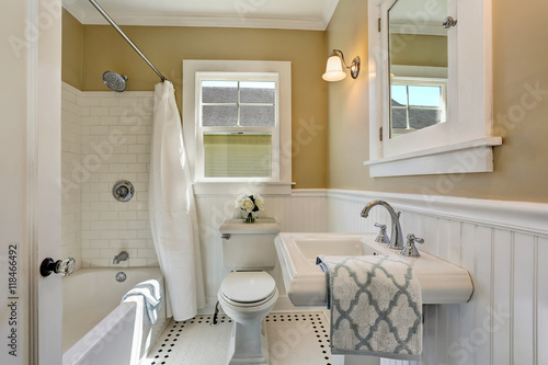 Valokuva  American bathroom interior in white tones and tile floor.