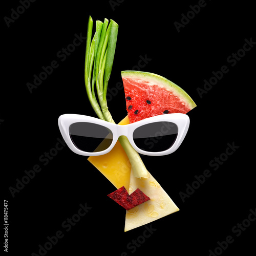 Fotografía  Fruity Picasso / Quirky food concept of Picasso style female face in sunglasses made of fresh fruits on black background