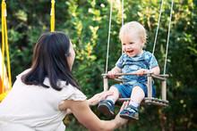Mom Swinging Her Baby Boy In S...