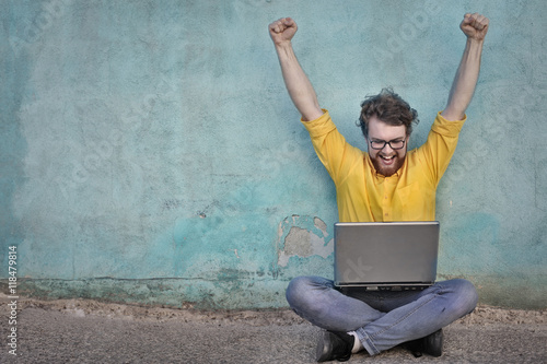 Jubilant man using a laptop