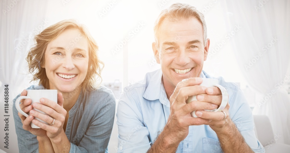 Fototapety, obrazy: Smiling middle aged couple sitting on the couch having coffee