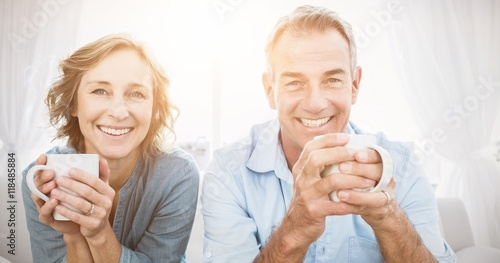 Obraz Smiling middle aged couple sitting on the couch having coffee - fototapety do salonu