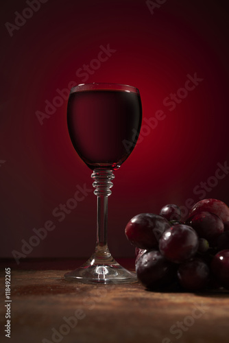 wine and grapes on a red background - 118492265