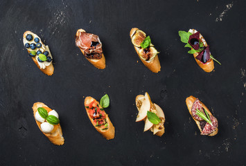 Italian crostini with various toppings on black plywood background, top view