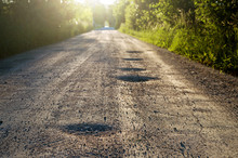 Bumpy Dirt Road With Holes Against Sunshine In Background. Shallow Depth Of Field.
