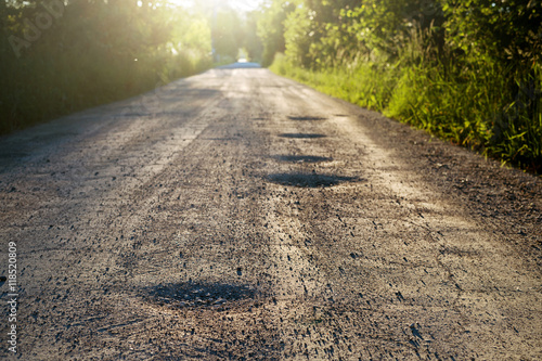 Fotografía  Bumpy dirt road with holes against sunshine in background
