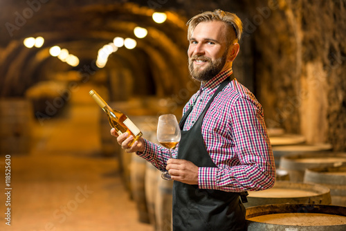 Portrait of a handsome sommelier in apron and checkered shirt with wine bottle standing in the old cellar. Maturing wine in oak barrels in underground natural cellar.