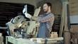 Carpenter makes selfie near woodworking machines in carpentry shop.