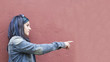 girl in pink wall pointing the finger
