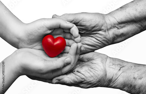 Fotografia  little girl and elderly woman keeping red heart in their palms t