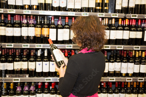 Photo  Woman holding bottles of wine in supermarket