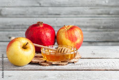 Zdjęcie XXL Granat, jabłka i miód na biały drewniany stół - tradycyjne symbole żydowskiego Nowego Roku, Rosz Haszana. Skopiuj miejsce