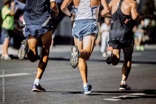 Zdjęcie XXL nogi męskie biegaczy biegną ulicami miasta podczas maratonu