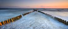 Coastal Sunset On The Baltic Sea, X-shaped  Wooden Groynes, Long Exposure, Rügen Island, Germany