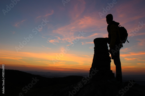 Obraz na płótnie Man standing next to a Cairn at the top of a mountain watching the sunrise in th