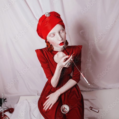 Fotografie, Obraz  redhead smoking girl with red lips and a red turban on a white background, woman