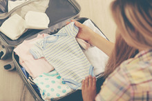 Pregnant Woman Packing Suitcase For Maternity Hospital At Home