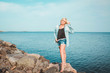 Tanned woman posing at the beach on summer day, looking up. Dreamy female in jeans clothes, standing rocky coast, blue sky background with sea. Concept holiday, outdoors. Travel active lifestyle.