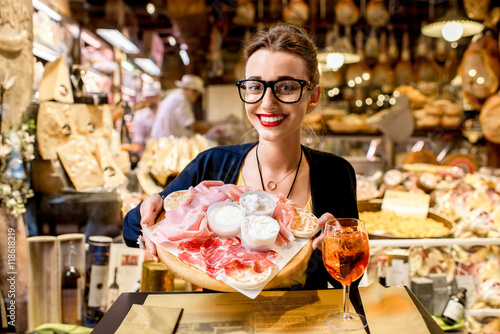 Fotografía  Young woman sitting near the food shop with traditional italian appetizer on the blurred food showcase background in Bologna city